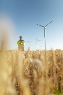 Portrait of smiling engineer standing in a field at a wind farm - GUSF01373