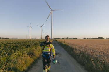 Technician walking on field path at a wind farm with climbing equipment - GUSF01376