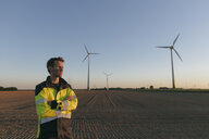 Engineer standing in a field at a wind farm - GUSF01379