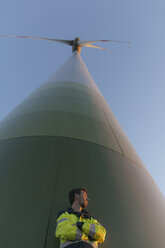Low angle view of engineer standing at a wind turbine - GUSF01382