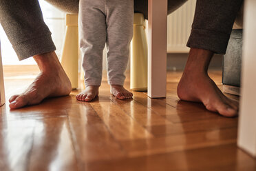 Father's and little daughter's feet barefoot on parquet - ZEDF01754