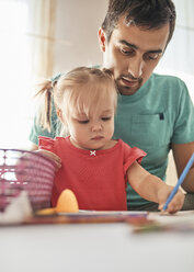 Portrait of little girl drawing with coloured pencil while her father watching her - ZEDF01757