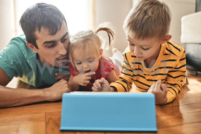 Father and his children lying on the floor at home using digital tablet - ZEDF01766