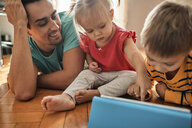 Father and his children using digital tablet at home - ZEDF01772