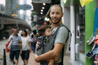 China, Hong Kong, portrait of father travelling with a little girl sleeping in a baby carrier - GEMF02518