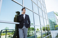 Businessman on cell phone outside office building - KIJF02095