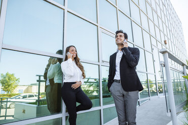Smiling businesswoman and businessman on cell phones outside office building - KIJF02098