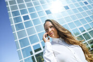 Smiling businesswoman on cell phone outside office building - KIJF02101