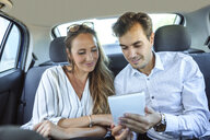 Couple using tablet on back seat of a car - KIJF02104