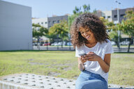Smiling young woman sitting on bench text messaging - KIJF02113