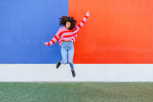 Happy young woman jumping in the air - KIJF02122