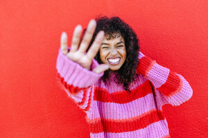 Portrait of laughing young woman in front of red wall - KIJF02125