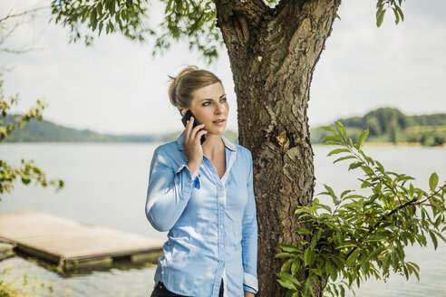 Woman on cell phone at a lake - MOEF01483