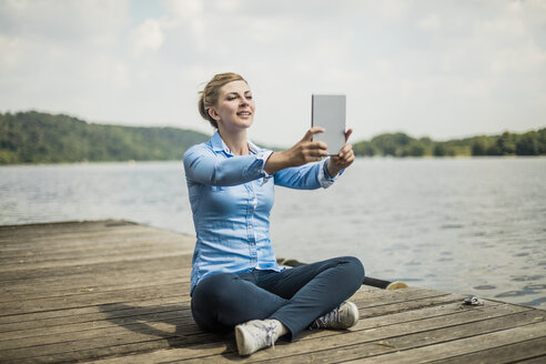 Smiling woman sitting on jetty at a lake taking a selfie with a tablet - MOEF01486