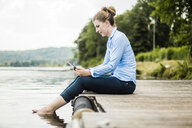 Woman sitting on jetty at a lake using tablet - MOEF01492