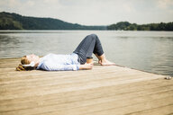 Woman lying on jetty at a lake with headphones and takeaway coffee - MOEF01504