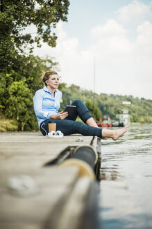 Woman sitting on jetty at a lake with tablet - MOEF01507