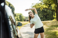 Sportive young woman stretching and using cell phone at a car in a park - MOEF01510
