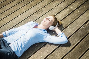 Woman lying on planks wearing headphones - MOEF01513