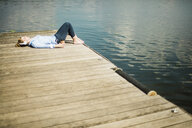 Woman lying on jetty at a lake with headphones and takeaway coffee - MOEF01516