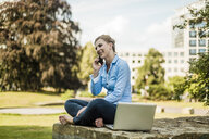 Smiling woman sitting in urban park talking on cell phone - MOEF01519