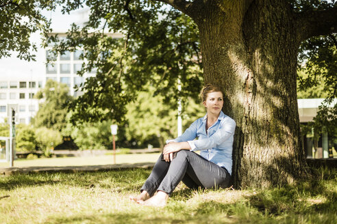 Woman sitting in urban park leaning against a tree - MOEF01522