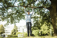 Woman in urban park at a tree wearing VR glasses - MOEF01525