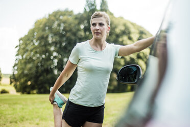 Sportive young woman stretching at a car in a park - MOEF01531