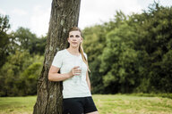 Sportive young woman leaning against a tree in a park holding bottle - MOEF01537