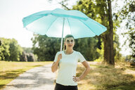 Sportive young woman standing in a park holding sunshade - MOEF01546