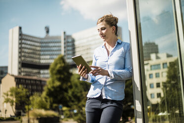 Smiling woman leaning against a building using tablet - MOEF01549