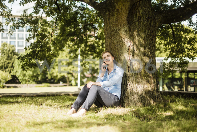 Woman sitting in urban park leaning against a tree talking on cell phone - MOEF01552 - Robijn Page/Westend61