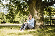 Woman sitting in urban park leaning against a tree talking on cell phone - MOEF01552