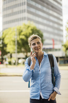 Smiling woman with backpack in the city talking on cell phone - MOEF01555