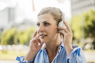 Portrait of smiling woman in the city wearing headphones - MOEF01558