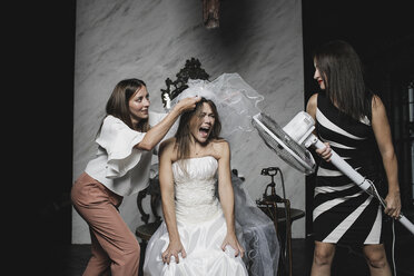 Playful friends and bride during wedding preparation - KMKF00617