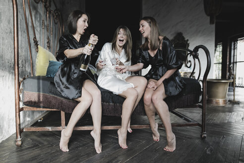 Three happy women sitting on bed drinking champagne together - KMKF00635
