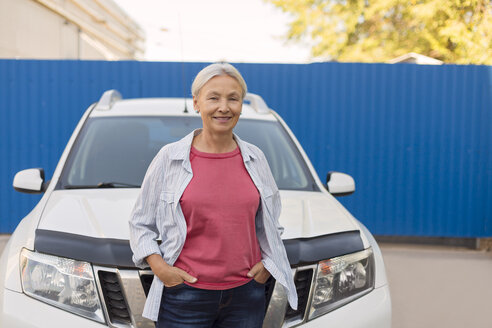 Portrait of smiling senior woman standing in front of her car - VGF00102