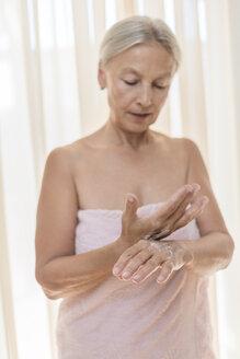 Senior woman applying cream on hands in the morning - VGF00108