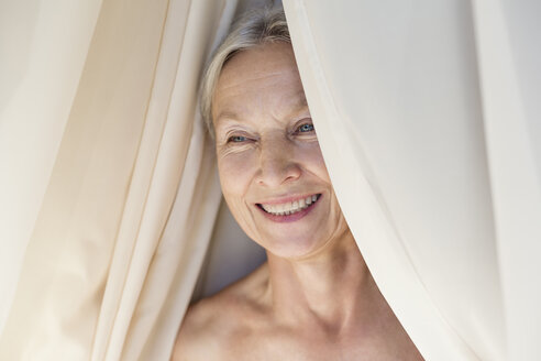 Portrait of relaxed senior woman behind curtain - VGF00111
