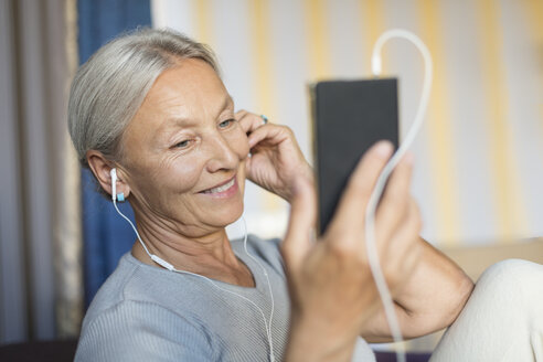 Portrait of smiling senior woman  listening music with earphones and smartphone - VGF00120