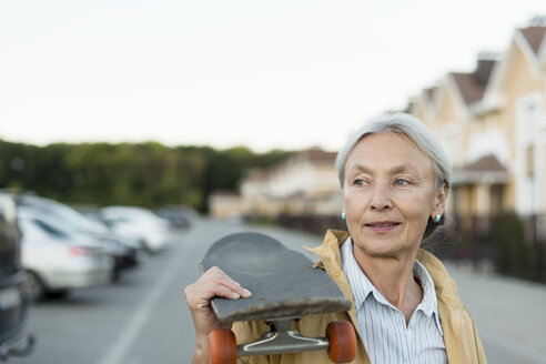 Portrait of senior woman with skateboard on her shoulder - VGF00135