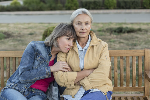 Portrait of senior woman sitting on a bench with her adult daughter - VGF00138