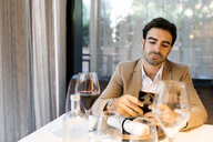 Man sitting at table in a restaurant using cell phone - VABF01641