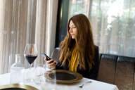 Woman sitting at table in a restaurant using cell phone - VABF01647