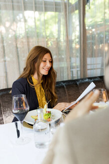 Smiling woman with man in a restaurant holding documents - VABF01656