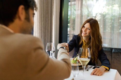 Smiling woman shaking hands with man and in a restaurant - VABF01659