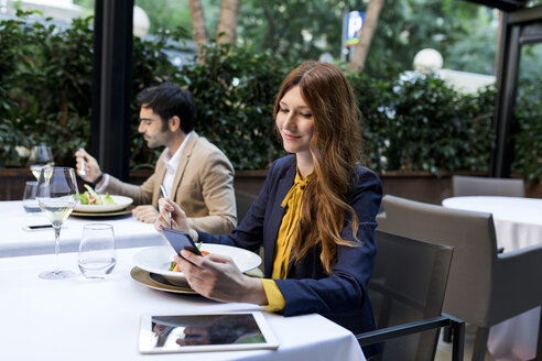 Man eating and woman using cell phone in a restaurant - VABF01665