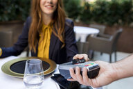 Woman paying with credit card in a restaurant - VABF01668