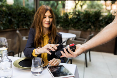 Woman paying with smartphone in a restaurant - VABF01671